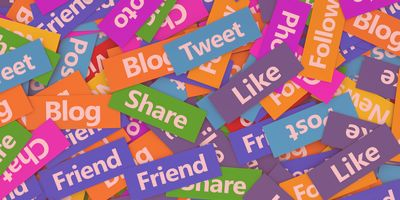 Social network, web and Internet concept background with a multitude of social media words, sign and text on colorful scattered paper.