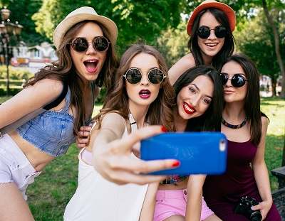 five beautiful young girls make selfie in the park